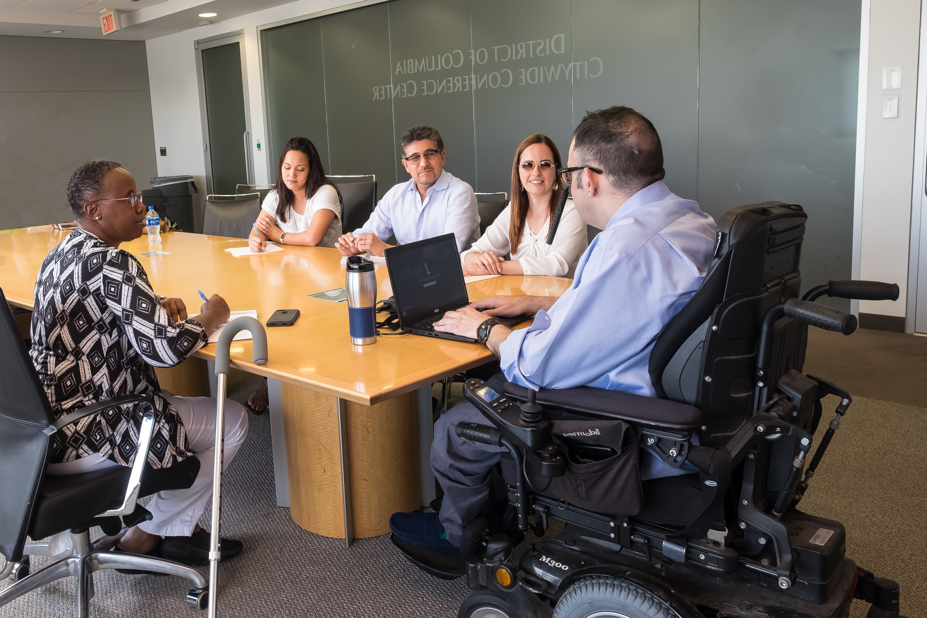 Group of 5 people with and without disabilities meeting around a table in the DC Citywide Conference Center