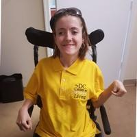 """Amber Keohane, a young Caucasian woman with cerebral palsy, who has shoulder-length brown hair, black sunglasses, hoop earrings, and a yellow """"DC Center for Living Independent"""" polo, sits in her wheelchair."""