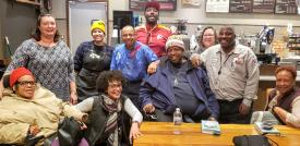 A group photo of Next Chapter Book Club participants at Peets Coffee - there are approximately 10 people in the photo and there is a mix of African American and White people.