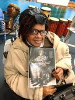 Thelma Green, a black woman who uses a wheelchair, holding up a magazine with her picture in it.