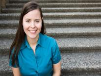 This is a head shot image of Alison Whyte. She is a white woman with brown hair, wearing a blue collared top, sitting on steps that extend up behind her, and smiling.